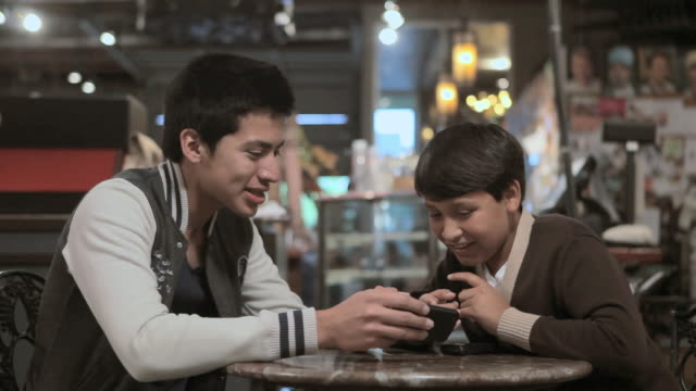 two brothers with smartphone in cafe - contented emotion stock videos & royalty-free footage
