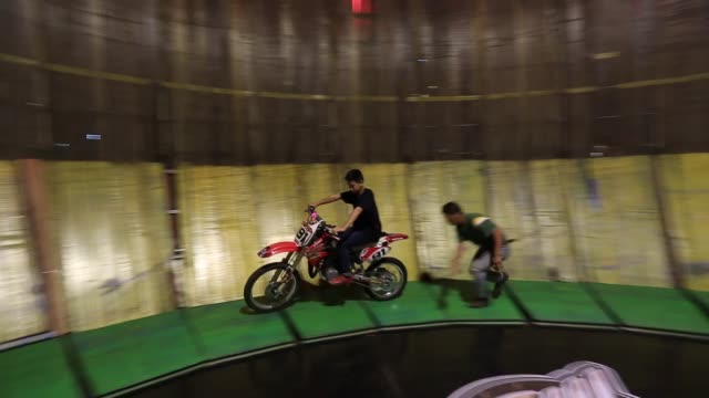 two brothers wutthipan and whuttipong kanlayanapan performs a vertical circular track well knows as the 'wall of death' with a motorbike trial during... - wall of death stock videos & royalty-free footage