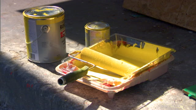 Two buckets of yellow paint one larger one small paint roller on paint tray w/ yellow paint all on sidewalk Painting redecorating house renovation...