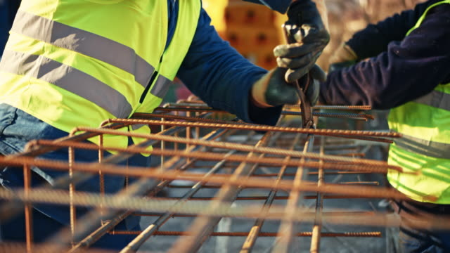 two builders tying rebars together - rod stock videos and b-roll footage