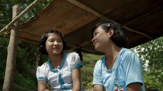 stockvideo's en b-roll-footage met m/s two burmese teenage girls (friends) talking - zonwering