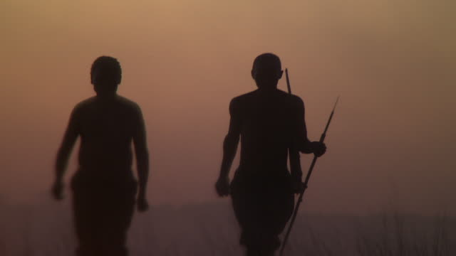 two bushmen hunters walk toward a bonfire. available in hd. - archery bow stock videos and b-roll footage