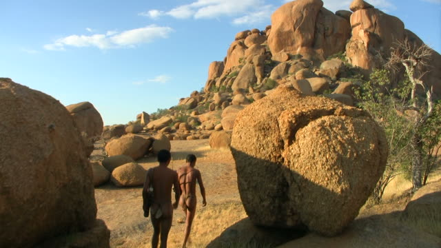 two bushmen walking - bulls_party_kran - rock face stock videos and b-roll footage