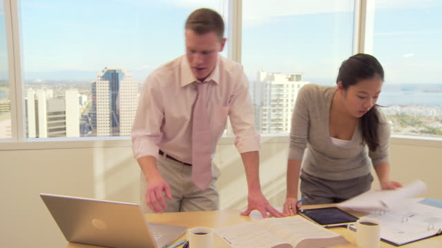 two business associates working  in office  - mitarbeiterengagement stock-videos und b-roll-filmmaterial