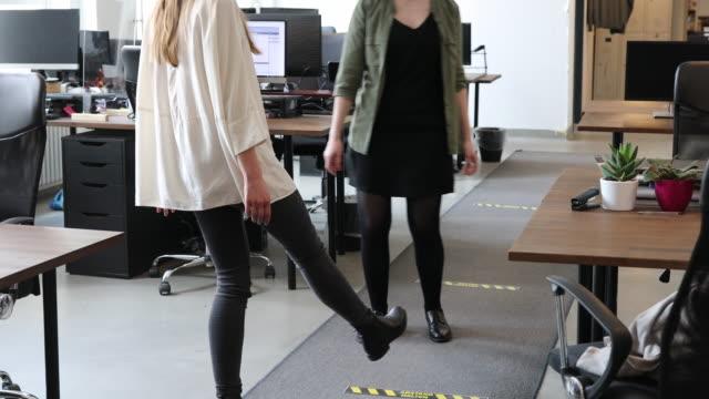 zwei geschäftskollegen grüßen sich gegenseitig mit einem fußstoß - greeting stock-videos und b-roll-filmmaterial