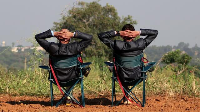 vídeos y material grabado en eventos de stock de dos socios de negocios relajarse al aire libre en la naturaleza - silla