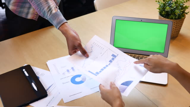 vídeos de stock e filmes b-roll de two business people analyzing financial report with green screen labtop - plus key