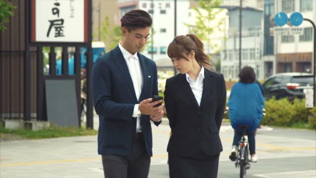 2 ビジネス人々 の会話を使用してスマート フォン (スローモーション) - 見る点の映像素材/bロール
