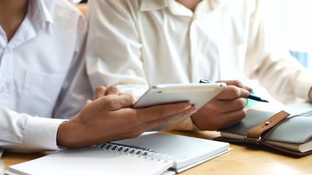 vidéos et rushes de deux affaires les gens discuter de travaux sur tablette numérique - collègue de bureau