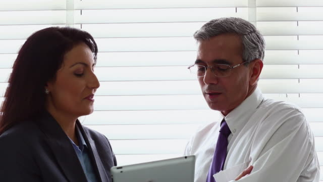 Two business people holding a digital tablet and discussing