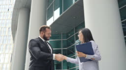 Two business people man and woman shaking hands outdoors near business center
