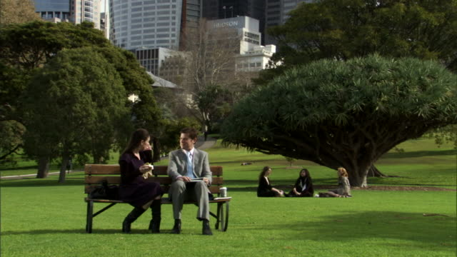ws, two business people meeting in park, office buildings in background, sydney, australia - ベンチ点の映像素材/bロール