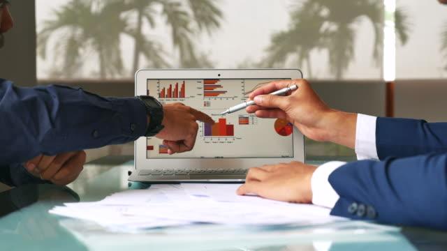 vidéos et rushes de deux gens d'affaires parlant présentation d'analyse d'affaires - graphique
