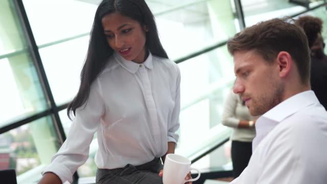 stockvideo's en b-roll-footage met twee mensen uit het bedrijfsleven praten in het kantoor - medewerkerbetrokkenheid