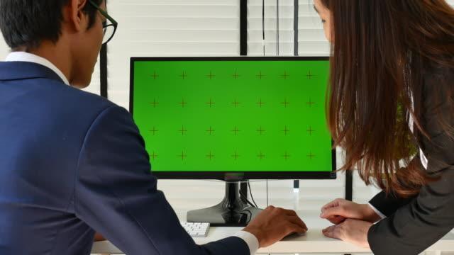 office のコンピュータグリーン画面で話す 2 人のビジネス関係者 - デザイナー点の映像素材/bロール
