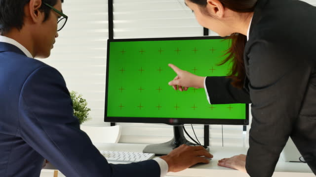 vídeos de stock e filmes b-roll de two business people talking to computer monitor with green screen, chroma key - plus key