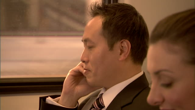 cu, selective focus, two business people traveling in train, sydney, australia - bahnreisender stock-videos und b-roll-filmmaterial