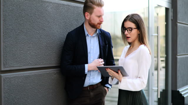 Två affärsmän använder digitala tablett utomhus