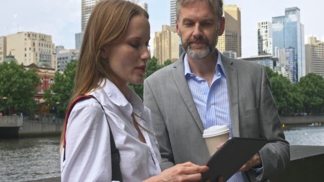 two business people with digital tablet talking in the street - business relationship stock videos and b-roll footage
