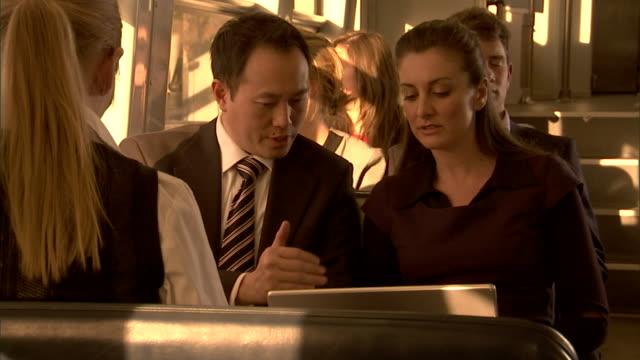 CU, Two business people working on laptop in train, Sydney, Australia