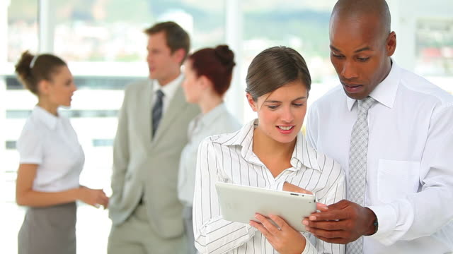 Two business people working together on a tablet