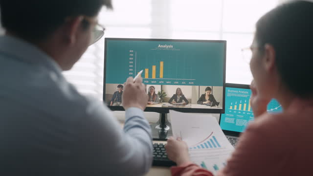 two business person discussing a financial graph report on the screen in video meeting with team in office - concept stock videos & royalty-free footage