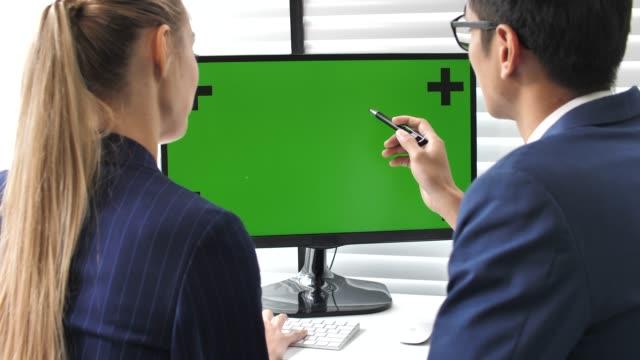 två business person som använder computer grön skärm i office - computer monitor bildbanksvideor och videomaterial från bakom kulisserna
