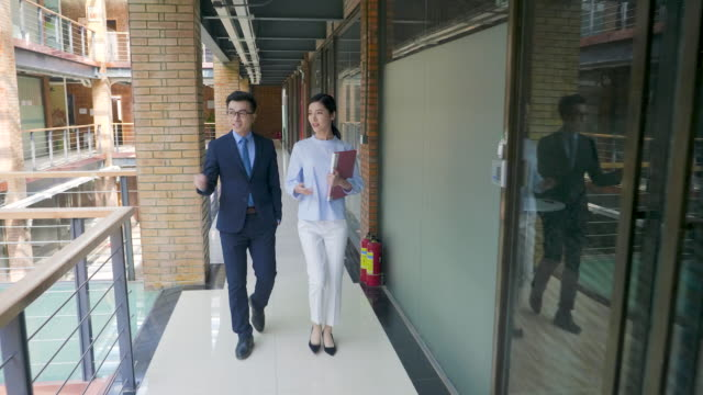 two business persons walking in office - asian colleague stock videos & royalty-free footage