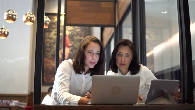 two business woman working at desk together - face to face stock videos and b-roll footage