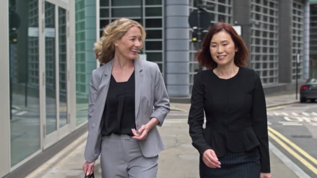 Two business women commuting in the street