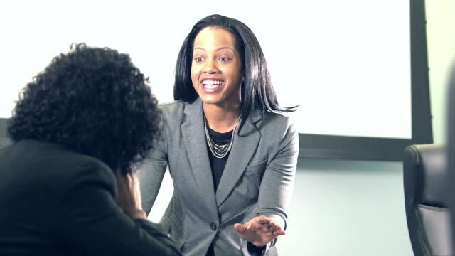 due donne d'affari che conversano in sala riunioni - strategia di vendita video stock e b–roll