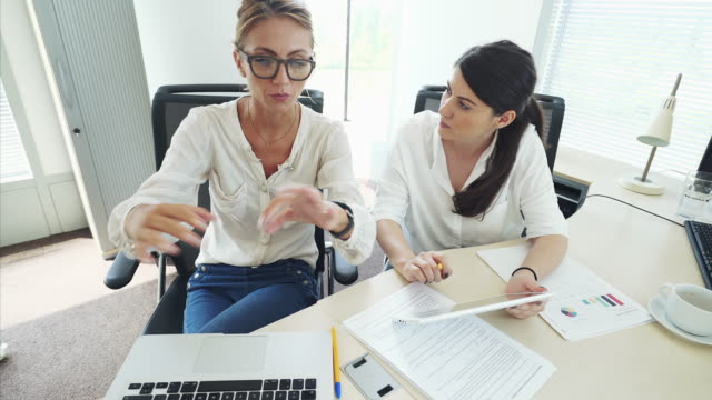 two business women discussing ideas. - determinazione video stock e b–roll