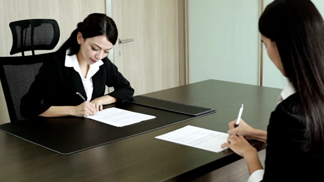 Two Business women hands writing sign up contract