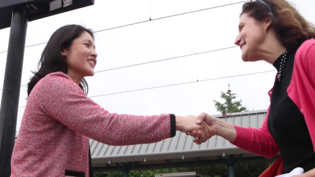 two business women meet and shake hands on train platform. - en dag i livet bildbanksvideor och videomaterial från bakom kulisserna