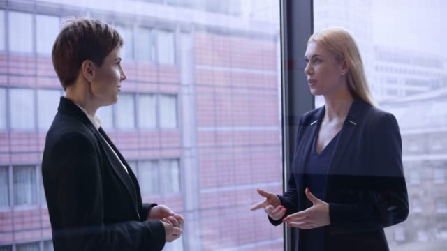 two business women talking in the glass corner office - two people stock videos & royalty-free footage