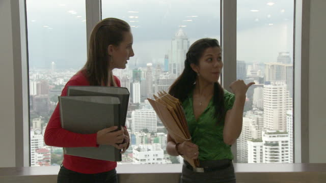 ms two business women talking, standing by window / bangkok, thailand - office politics stock videos & royalty-free footage