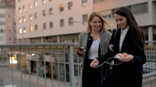 ms two business women using their smartphones while walking in the city - colleague stock videos & royalty-free footage