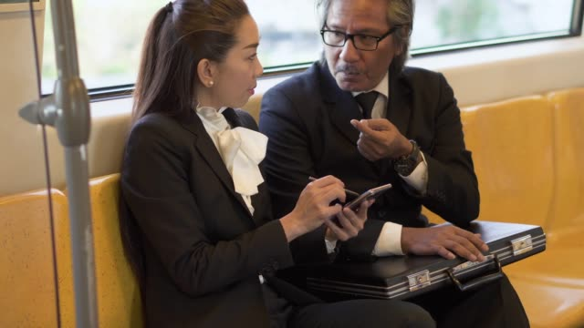 two business working and discussion with smart phone in the train. - on the move stock videos & royalty-free footage
