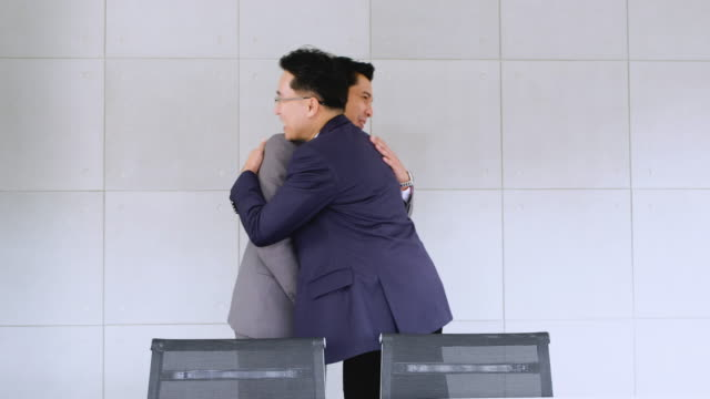 two businessman greeting with handshake and hug each other in conference meeting room. - colleague hug stock videos & royalty-free footage