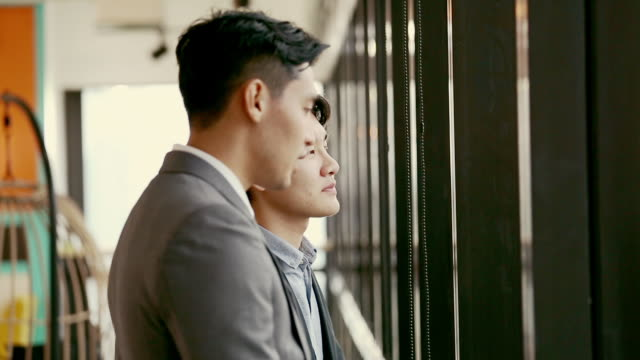 兩位商人站在辦公室與團隊合作交談,在辦公室的咖啡休息,看著窗外 - 全套西裝 個影片檔及 b 捲影像