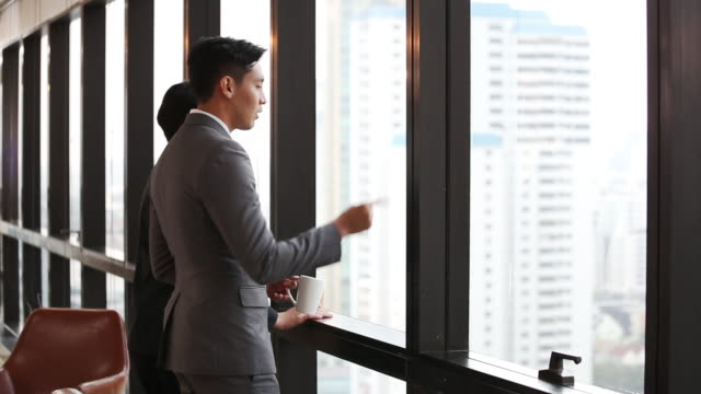 オフィスでコーヒーブレイクとしてチームワークを持って立ち、窓の外を見て話す2人のビジネスマン - global business点の映像素材/bロール