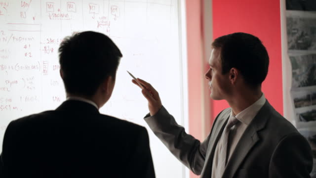 MS Two businessmen discussing and pointing on whiteboard / China