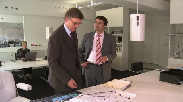 stockvideo's en b-roll-footage met ms two businessmen discussing blueprints and shaking hands while businesswoman work on laptop in background / berlin, germany - vrouw met een groep mannen