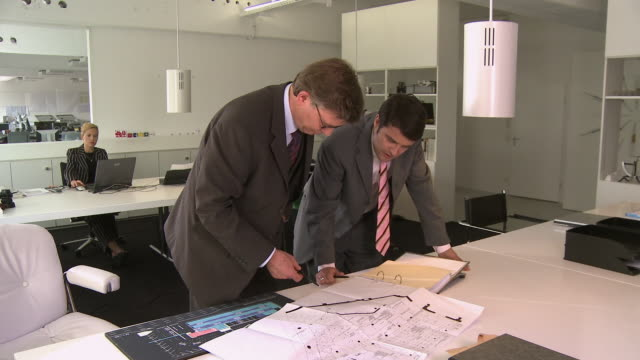 ms two businessmen discussing blueprints at office desk while businesswoman work on laptop in background / berlin, germany - employee engagement stock videos & royalty-free footage
