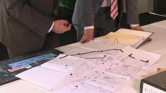 vidéos et rushes de ms tu two businessmen discussing blueprints / berlin, germany - tenue d'affaires formelle