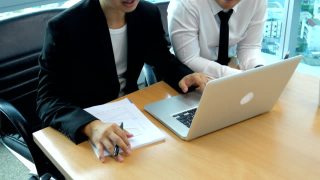 Two Businessmen Discussing Work on Laptop in Meeting Room