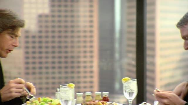 ms pan two businessmen eating lunch in office, los angeles, california, usa - hel kostym bildbanksvideor och videomaterial från bakom kulisserna