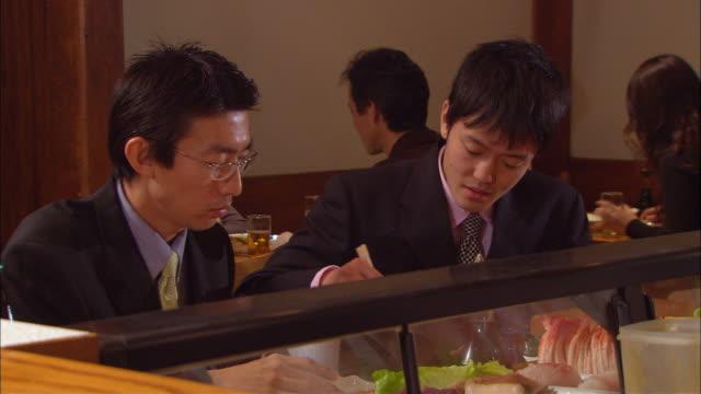 cu, two businessmen eating sushi in bar - skåp med glasdörrar bildbanksvideor och videomaterial från bakom kulisserna