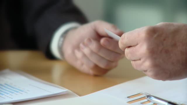 ECU, SELECTIVE FOCUS, Two businessmen exchanging business card at conference table, close-up of hands, Berlin, Germany