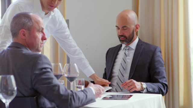ms two businessmen having meeting in restaurant server bringing food to table. - business lunch stock videos & royalty-free footage